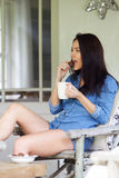Relaxed young woman with a cup of coffee and eating cookies. Portrait of a relaxed young woman with a cup of coffee and eating cookies at home Stock Photography