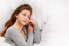 Young woman dreaming in bed. Relaxed young woman dreaming in bed in morning. with copy space on right Royalty Free Stock Photography