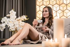 Relaxed young woman drinking herbal tea before spa treatment. Relaxed young woman drinking herbal tea while sitting on sofa before spa treatment in wellness royalty free stock photos