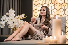 Relaxed young woman drinking herbal tea before spa treatment Royalty Free Stock Image