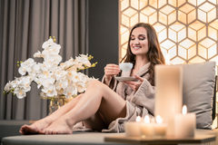 Relaxed young woman drinking herbal tea before spa treatment. Relaxed young woman drinking herbal tea while sitting on sofa before spa treatment in wellness Royalty Free Stock Image