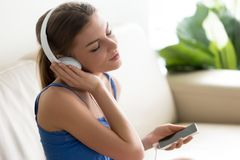 Relaxed young woman enjoying music in headphones using mobile ap. Relaxed calm young woman enjoys music, teenager wearing headphones listens to high quality Stock Photos