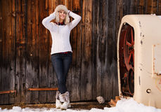 Relaxed young woman in furry hat standing near rustic wood wall Stock Images
