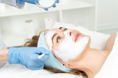 Relaxed young woman is getting facial skin care treatment at bea royalty free stock image