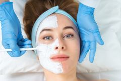 Relaxed young woman is getting facial skin care treatment at bea royalty free stock images