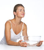 Relaxed young woman with glass bowl with water Royalty Free Stock Image