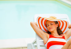 Relaxed young woman in hat laying on sunbed Stock Images