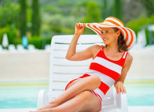 Relaxed young woman in hat sitting on sunbed Royalty Free Stock Photography