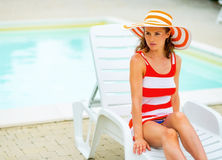 Relaxed young woman in hat sitting on sunbed Royalty Free Stock Photos