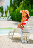 Relaxed young woman in hat sitting on sunbed Royalty Free Stock Images