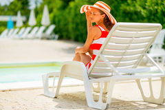Relaxed young woman in hat sitting on sunbed Stock Image