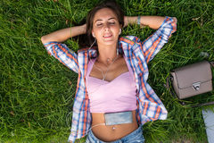 Relaxed young woman with headphones listening to music from a smartphone and lying on the grass her eyes closed Stock Photography