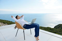 Relaxed young woman at home working on laptop Royalty Free Stock Photo