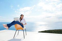 Relaxed young woman at home working on laptop Royalty Free Stock Photography