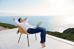 Relaxed young woman at home working on laptop Stock Images