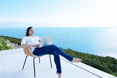 Relaxed young woman at home working on laptop Stock Image