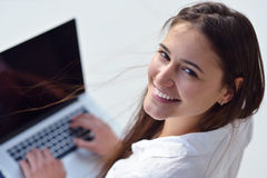 Relaxed young woman at home working on laptop computer Royalty Free Stock Photo