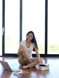 Relaxed young woman at home working on laptop computer Stock Photo