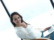 Relaxed young woman at home working on laptop computer Stock Photography