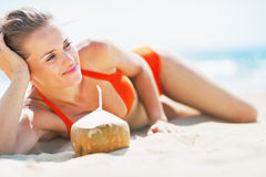Relaxed young woman laying on beach with coconut Stock Images