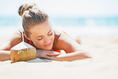 Relaxed young woman laying on beach with coconut Stock Photography