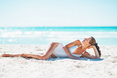 Relaxed young woman laying on beach stock photography