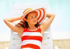 Relaxed young woman laying on chaise-longue Royalty Free Stock Images