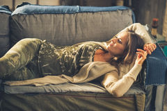 Relaxed young woman laying in loft apartment Stock Image