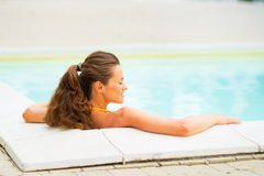 Relaxed young woman laying in pool Stock Images