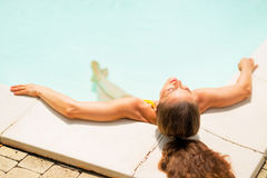 Relaxed young woman laying in pool Royalty Free Stock Images