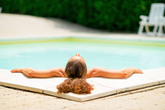 Relaxed young woman laying in pool Stock Image