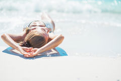 Relaxed young woman laying at seaside. rear view Royalty Free Stock Photos
