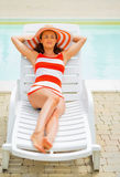 Relaxed young woman laying on sunbed Royalty Free Stock Photography