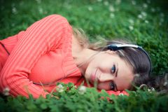 Relaxed young woman listening music. Cat clover meadow Royalty Free Stock Photography