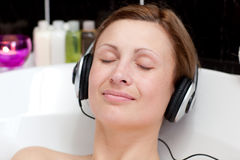 Relaxed young woman listening music in a bubble ba Stock Image