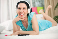 Relaxed young woman listening music with mobile phone in bed at Stock Photography