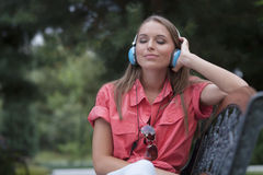 Relaxed young woman listening to headphones on park bench Stock Photography