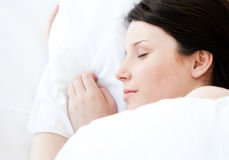 Relaxed young woman lying in a bed sleeping Royalty Free Stock Photography