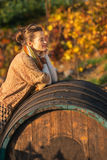 Relaxed young woman near wooden barrel Royalty Free Stock Photo