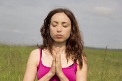 Relaxed young woman outdoors in nature doing meditation royalty free stock photography