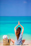 Relaxed young woman practicing yoga outdoors at white beach Stock Photos