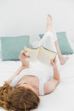 Relaxed young woman reading a book in bed Royalty Free Stock Photography