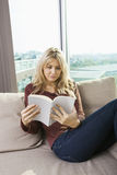 Relaxed young woman reading book in living room at home Stock Image