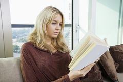 Relaxed young woman reading book in living room at home Royalty Free Stock Photos