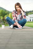 Relaxed young woman reading a book while sitting down Royalty Free Stock Photo