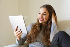 Relaxed young woman reading a message, e-book or information on royalty free stock image