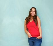 Relaxed young woman in red shirt smiling with hands in pocket Stock Photography