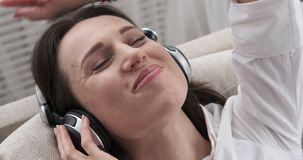 Happy woman singing and listening to music on headphones stock footage