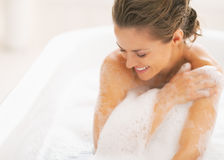 Relaxed young woman sitting in bathtub. Relaxed young woman with brown hairs sitting in bathtub royalty free stock image