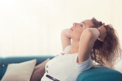 Relaxed young woman sitting on a couch daydreaming Stock Image